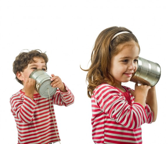 boy-and-girl-talking-on-a-tin-phone-isolated-on-white-576x493