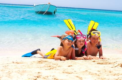 three-kids-at-beach-in-snorkeling-gear